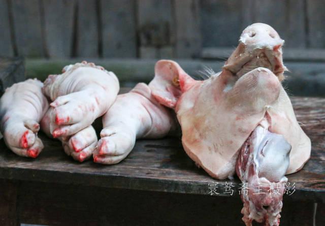 """猪头和四只猪脚放在旁边,砍得非常整齐,也收拾的非常干净,看来这个""""女图片"""