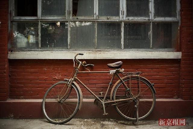 2017年5月2日,幸福北里,一辆锈迹斑斑的老式自行车停在一栋老居民楼前图片