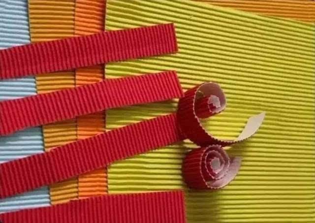 1.将瓦楞纸剪成长条,然后卷成圆形,压扁,如图粘贴在一起.