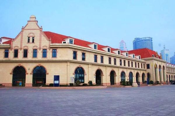 踏入青岛火车站的这一刻,你就已经走进了这座城的历史中。始建于20世纪初德占时期,一座饱经沧桑的百年老站,本身就是一件艺术品。远远望去它不似车站,倒像是一座庄园,复古文艺的红瓦黄墙,造型柔美的拱形门窗,尽显欧式韵味。广场前高高的尖顶钟楼,看着眼前行色匆匆的旅人,刹那间以为自己走进了老电影里的镜头。来青岛,很多人大概就是为了看那一片海,而火车站距离大海只有两百多米,那么,第一站不如就先来听听这座城市的海浪声吧。   地址:青岛市市南区泰安路2号    苏州火车站- 引入苏州古典园林设计理念