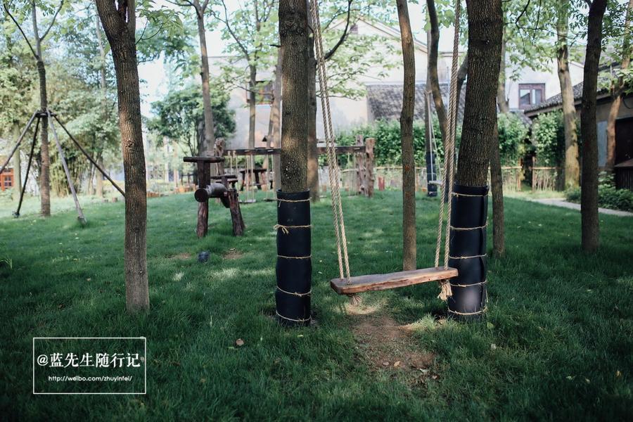 村口那块小空地上的木质的秋千和跷跷板,不由自主的想去体验一番,仿佛图片