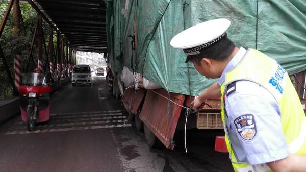 看到在高速公路施工搭建的龙门架下卡着一辆渝af30xx