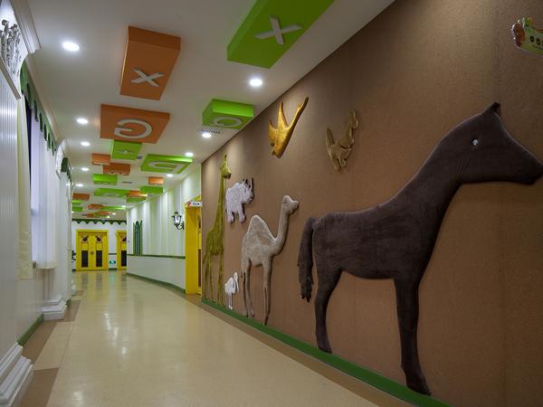 幼儿园在装修前期的设计当中,设计师就应该考虑到如何通过完美的艺术表现来进行设计。只有通过前期的设计,根据设计师的效果图表现,在后期装修的过程中,就要通过装修材料和造型来表现出来。幼儿园走廊设计要连贯通畅,尽量保证走廊的宽度在1.2米以上。边上的围栏最好是密封型的,围栏高度不能低于1米,围栏在体现建筑特点上有一定的作用,因而造型要多样且具有幼儿园特点。可打破传统的平直封闭形式,有凹凸变化,可增加围栏的趣味性,也可以设计成上部分通透、下部分封闭的形式,但要防止幼儿攀爬两边墙面。当走廊宽大时,在不影响通道