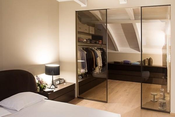 阁楼装修成卧室,用玻璃门隔断圆弧形的部分,作为衣帽间.