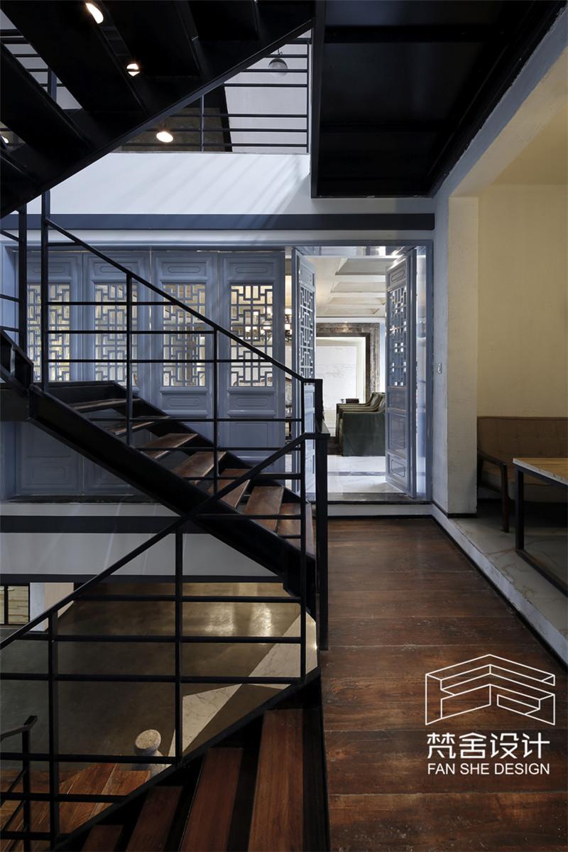 一楼中厅为改造后的楼梯间,深色钢结构衬底,斑驳的老木头切割后上