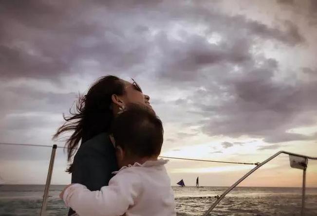 章子怡在微博上po出一张她在海边抱着女儿醒醒吹风的照片,章子怡迎着
