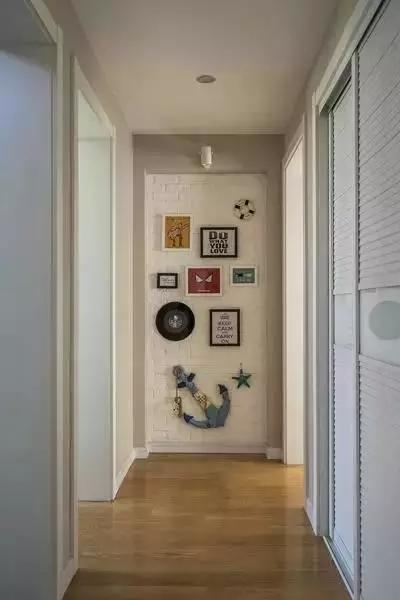 过道尽头做了端景设计,文化石小白砖搭配童趣十足的海星,船锚和相片墙图片