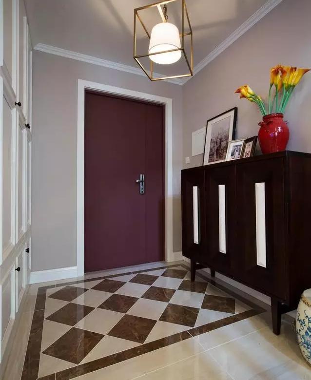地面拼花地砖画出了玄关区域,一个钟鼓凳,入户门美观实用兼图片