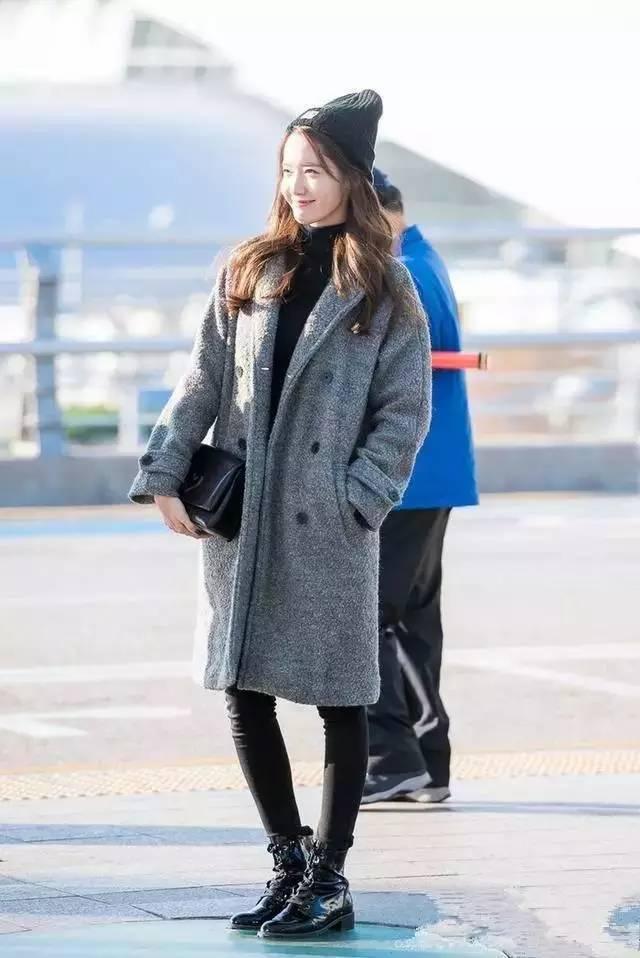 头戴黑色针织冷帽,身穿灰色呢大衣内搭黑色高领针织衫,下穿机车靴简约时髦.图片