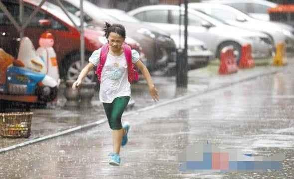 昨日,一名放学的孩子在雨中奔跑.