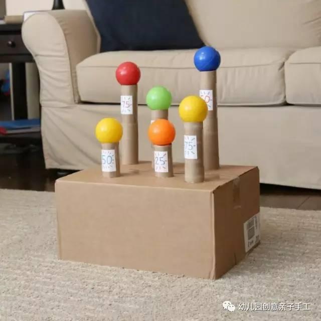 不同高度卫生纸筒在纸箱中固定好,把乒乓球放置于卫生纸筒上,幼儿尽心图片