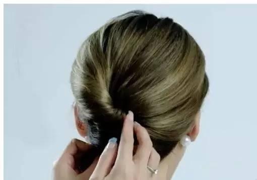 用手抓起头发,再用梳子梳理头发.图片