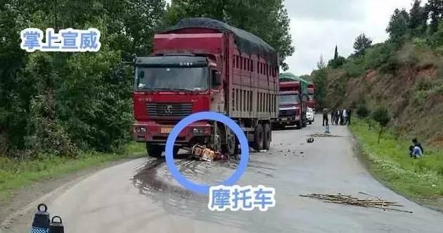 一辆大货车与摩托车发生碰撞,致使摩托车和驾驶人被压在大车轮胎下.图片