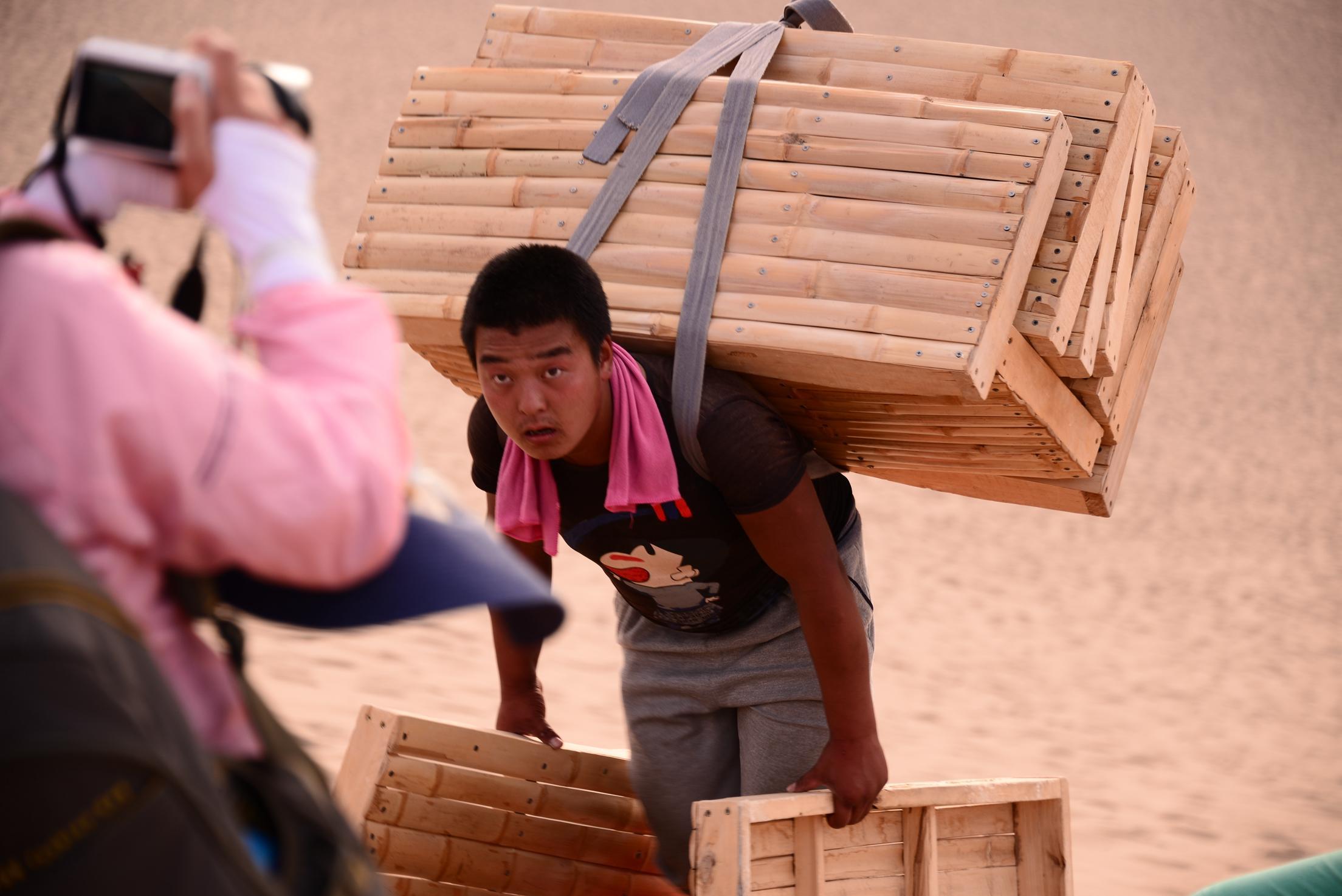 月牙泉脚夫每天给游客背100斤滑沙竹板上山近百趟