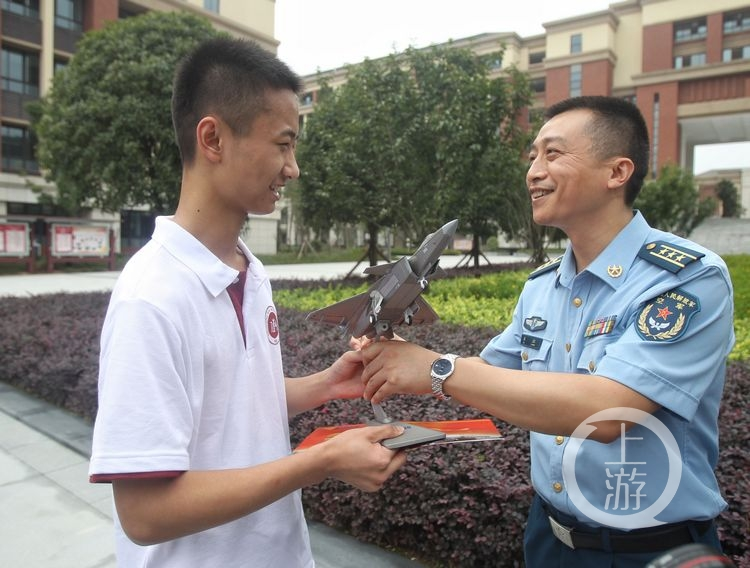 李成林从空军招飞工作人员手中接过录取讯息书和战机模型.图片