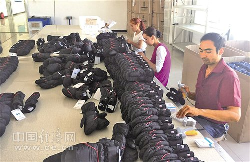 手套厂车间�_喀什中兴手套有限公司生产车间内,维吾尔族员工们正在生产.