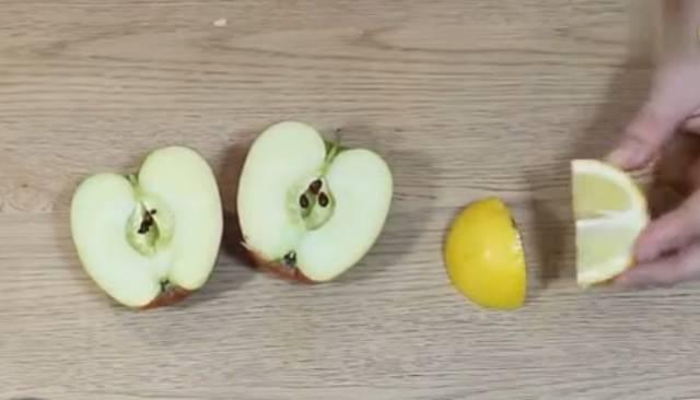 把一个苹果对半切开,然后把柠檬切成四块.图片